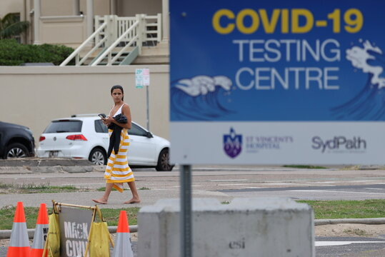A beachgoer walks past a COVID-19 testing centre at Bondi Beach in Sydney