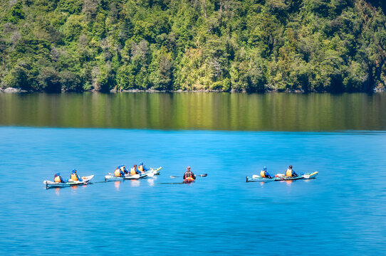 People enjoying kayaking in the pristine waters of the Deep Cove at Doubtful Sound, a fjord in New Zealand, South Island.