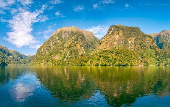 Sunlit mountain range alpine panorama and reflections in the water in the fjord wilderness at Doubtful Sound in New Zealand, South Island.