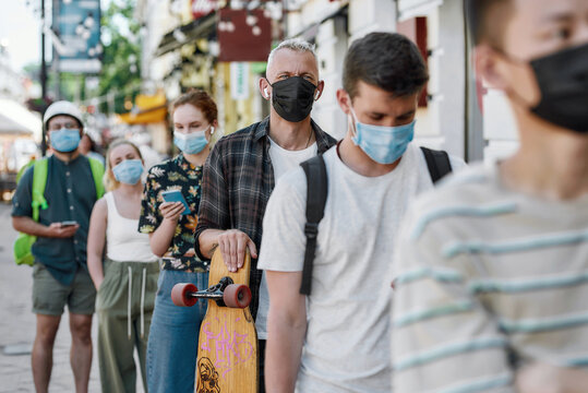 Middle aged man holding longboard, wearing mask waiting, standing in line, respecting social distancing to collect his takeaway order from the pickup point during lockdown