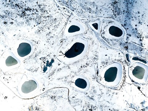 Aerial View Of Ponds On Snow Covered Filed