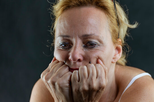 Middle-aged white woman is crying with her face resting on her hands and has makeup dripping from her eyes