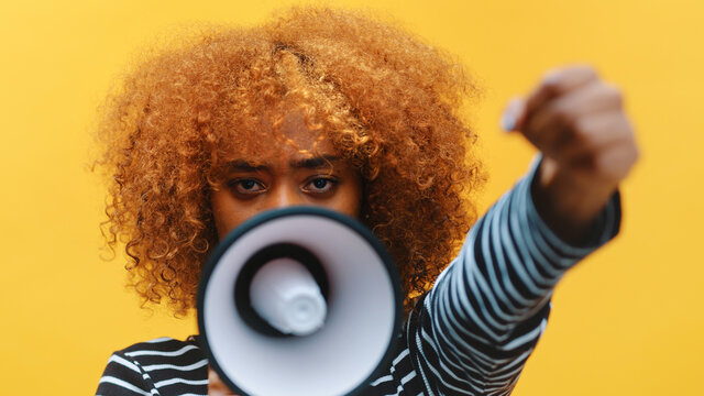African american black woman with curly hair shouting into the loudspeaker. High quality photo