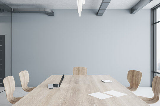Minimalistic conference interior with large wooden  meeting table and chair.