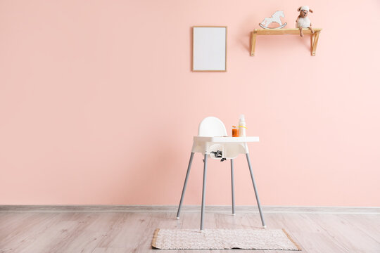 Modern interior with baby highchair on color background
