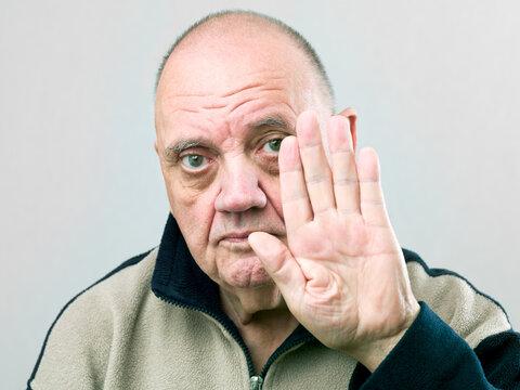 portrait vieil homme faisant signe stop avec la main