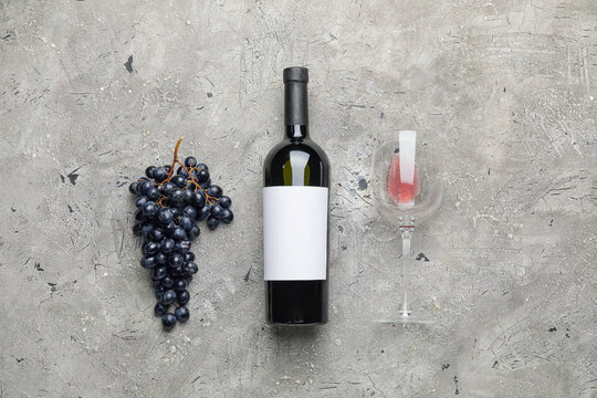 Tasty red wine with fresh grapes on grunge background