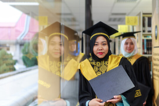 Portrait Of Young Friends With Certificate During Ceremony