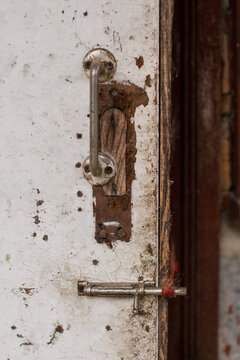 old metal handle on a dirty white door