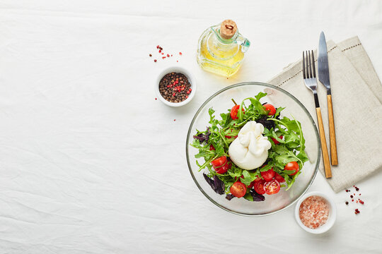 Burrata, Italian fresh cheese made from cream and buffalo or cow milk, with tomato, arugula and red basil salad