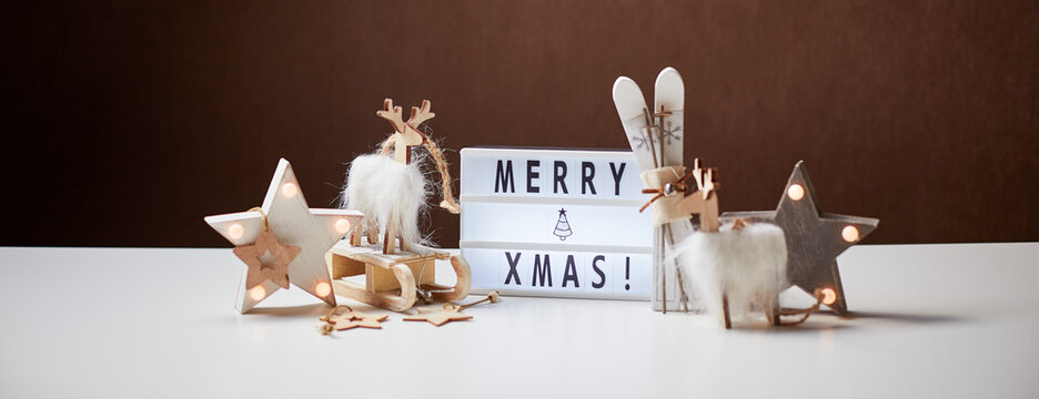 New Year or Christmas composition. Light box inscription Merry Xmas and wooden ornaments, copy space.