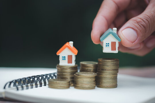 A woman holding a house on a pile of coins is planning savings money. concept for property ladder, mortgage and real estate investment. for saving or investment for a house.
