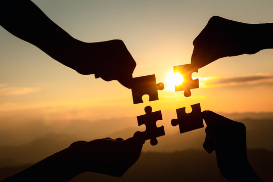Silhouette  hands connecting  jigsaw puzzle piece against sunrise, Business solutions,  teamwork, partnership, success, goals and strategy concepts.