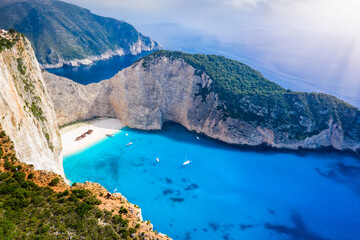 Aerial view to the fluorescent, blue sea of the popular Navagio shipwreck beach on the Greek island of Zakynthos on a summer day with low clouds