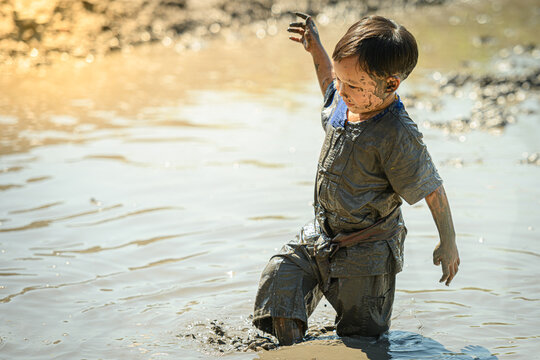 Thai asian child  boy Playing Mud in cornfield on sunny Ddy