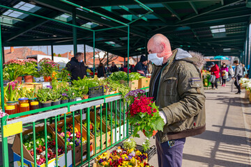 Merchandiser in medical mask and gloves is selling potted flowers Fototapete