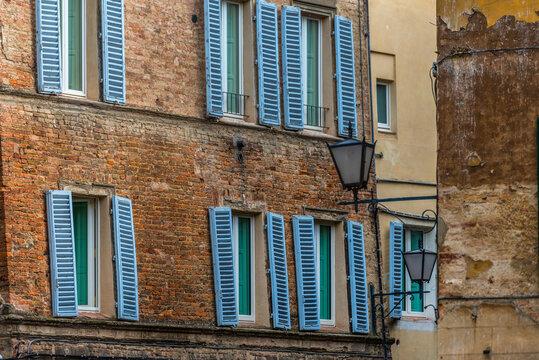 Schief hängende Fensterläden in der Altstadt von Siena, Italien