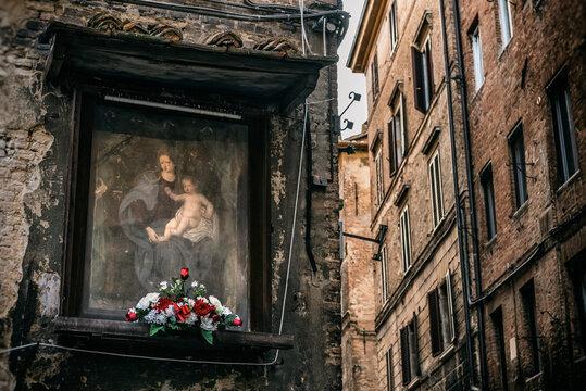 Mit Blumen dekoriertes Heiligenbild in Siena, Italien