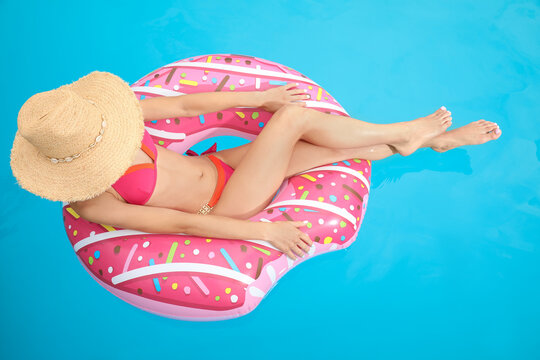 Young woman wearing stylish pink bikini on inflatable ring in swimming pool, above view