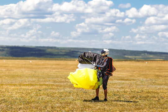 Landing. Freedom as a way of life. Skydiver landed in the wheat field. Parachutist in professional equipment. Team of extreme active sports