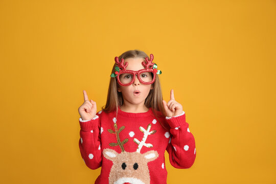 Surprised little girl in Christmas sweater and party glasses pointing on yellow background