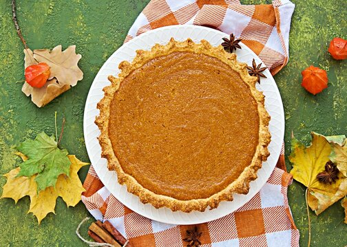 A traditional American Thanksgiving dessert, a whole pumpkin pie on a light plate against a green concrete backdrop. Thanksgiving day concept. Pumpkin recipes. Top view.