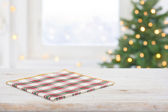Checkered napkin on table and frosty window with christmas tree