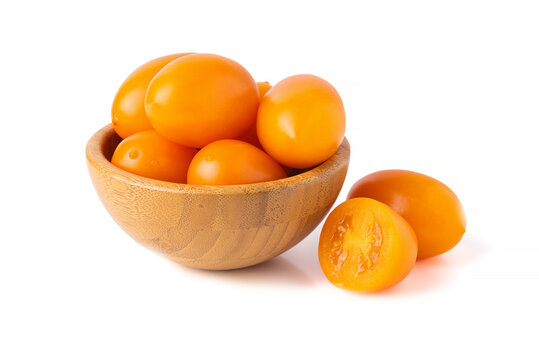yellow tomatoes in wooden bowl