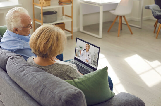 Older couple is sitting at home in the living room and talking to their family doctor via video link