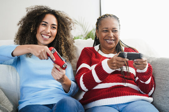 Mother and daughter playing video games at home - Family people having fun with new technology console online - Happiness and gaming concept - Focus on mum face