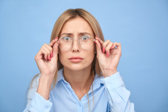 OMG! I don't believe you. Studio shot blonde girl with puzzled face and bulging eyes holds hands on the rim of glasses, emotional reaction to unexpected news isolated on blue background