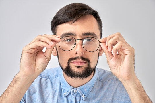 Studio shot caucasian bearded man with poor eyesight holds hands on the rim of glasses and squints, trying to see something, looking at the camera isolated on blue background