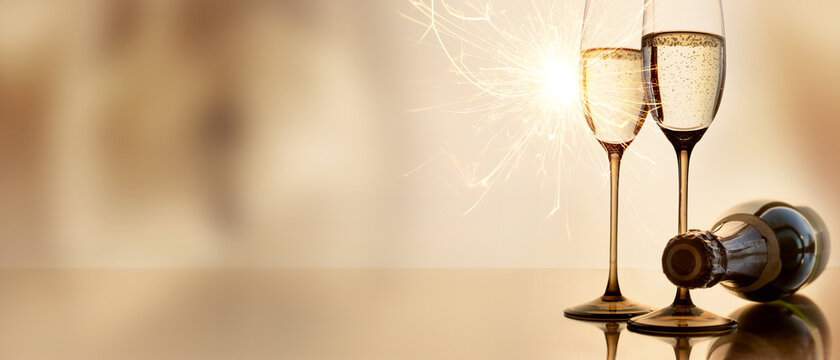 Champagne for new year greetings. Abstract golden background with champagne glasses and sparkler. Concept for celebrations with space for text.
