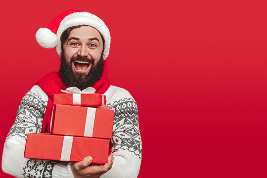 Delighted hipster man carrying stack of Christmas gifts