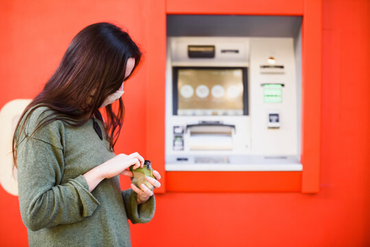 Young woman with a mask runs out of money next to a bank ATM.