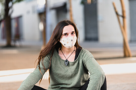 Young woman poses sitting on a street with a carefree face mask.