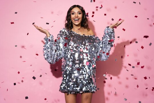 Cheerful beautiful girl wearing sparkle dress standing under confetti rain and celebrating isolated over pink background