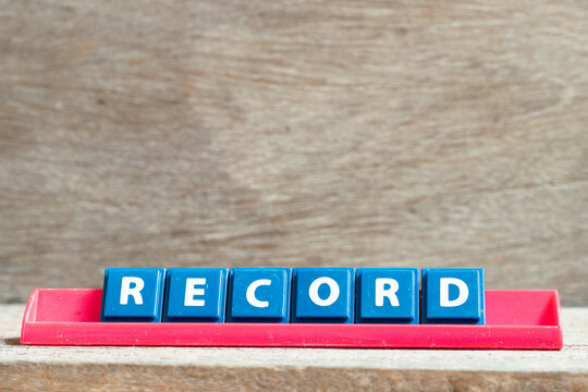 Tile letter on red rack in word record on wood background