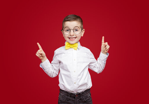 Cheerful stylish little boy pointing up