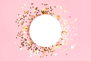 Round paper card mockup with frame made of gold stars confetti. Festive flatlay on a pink pastel background.