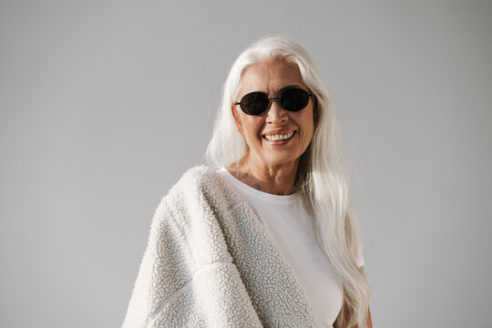 Joyful elderly white-haired woman in sunglasses smiling at camera
