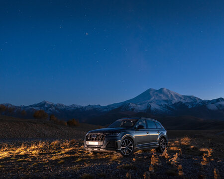 Dzhily Su, Caucasus, Russia October 11, 2020. Modern car Audi SUV stands at night against the background of Mount Elbrus.