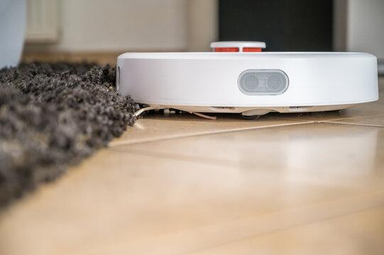 Saugroboter fährt eine hohe Teppichkante entlang
