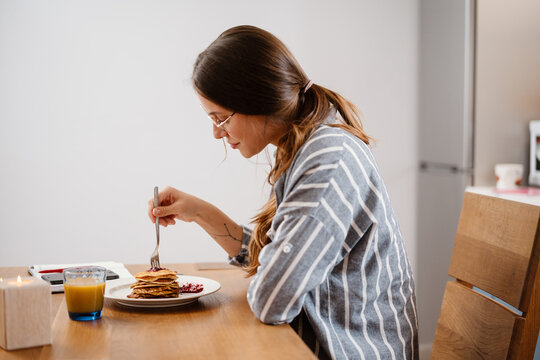 Pleased beautiful woman eating pancakes while having breakfast