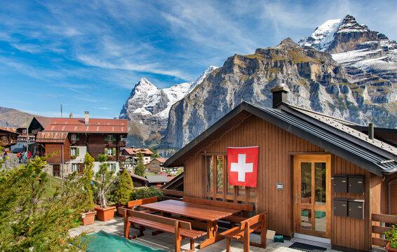 Wood chalet with Swiss flag in mountain village Murren at Jungfrau region, Switzerland.