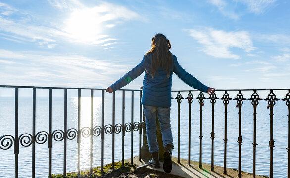 Frau mit Blauer Daunenjacke am Geländer an einem See