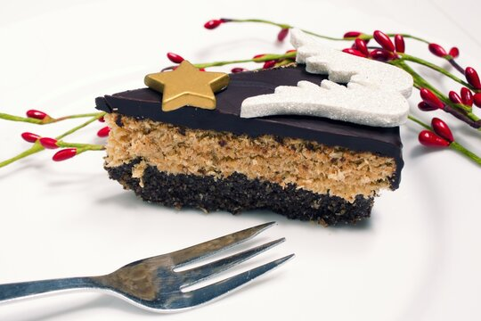 A piece of coconut cake with chocolate prepared from quality and healthy ingredients. The cake is decorated with wings and a star.Christmas healthy cake made of coconut, 90% chocolate, almonds, stevia