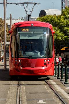 Red Sydney light rail tram on tracks in city street