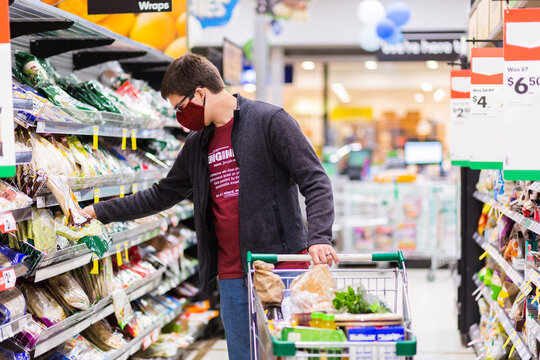 Young male person grocery shopping for essentials with face mask protection from spreading covid-19