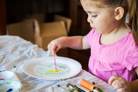 Little girl in pink painting on a paper plate